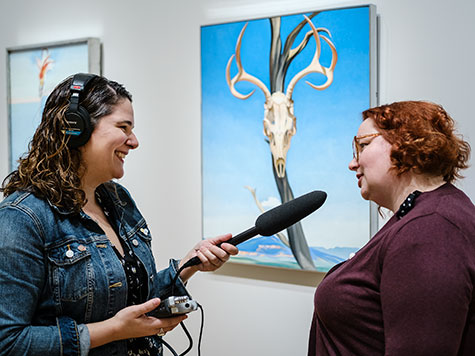 Tamar Avishai interviews a visitor for her podcast while they stand in front of a Georgia O'Keeffe painting of a deer skull suspended on a branch with a mountain landscape in the distance