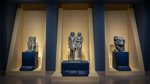 Three ancient Egyptian sculptures stand in individual yellow niches in a blue gallery. From left to right: a pharaoh, a god, and a woman; a pharaoh and queen; and fragments of three figures.