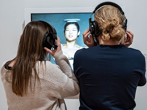 Two visitors listening two video piece, depicting person with dish on top of head