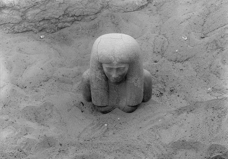 Black and white: the statue of Lady Sennuwy lies in the ground with sand covering the figure up to its shoulders.