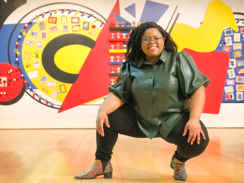 """Chanel Thervil poses in front of """"Community Arts Initiative: Patterns of Greatness"""""""