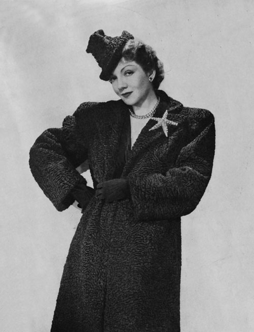 A woman stands with her left arm on her hip and right arm draped across her torso.  She wears a fur hat, a fur coat, and a starfish-shaped brooch pinned to the left lapel.