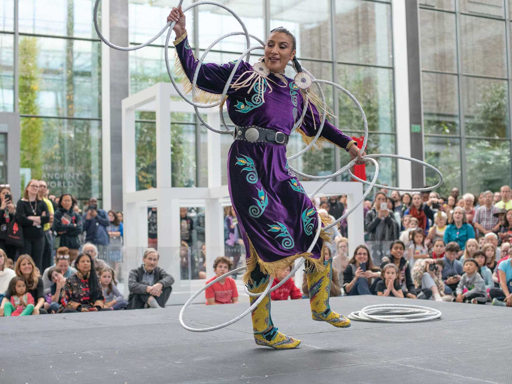 Dancer with hoops performing in front of an audience in Shapiro Family Courtyard