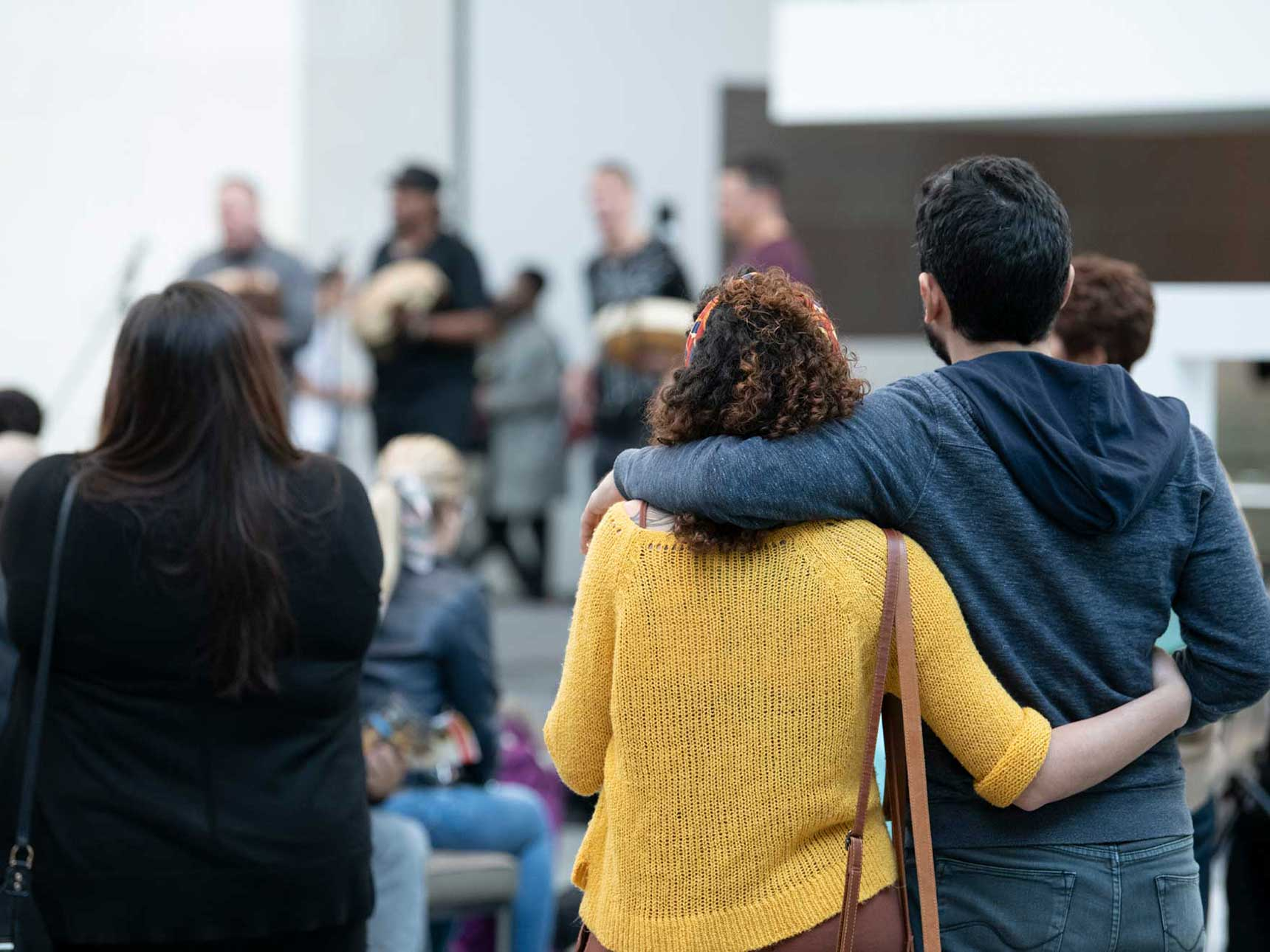 Couple in side-by-side embrace watching performance in Shapiro Family Courtyard
