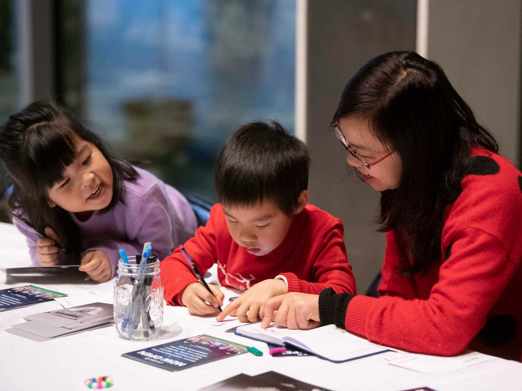 Parent engaged with two children working on art project at table