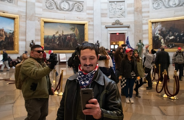 Rioters stand before John Trumbull's paintings of scenes from American history in the Capitol Rotunda on Wednesday, January 6, 2021.
