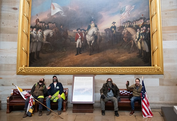 Rioters sit beneath John Trumbull's painting of Lord Cornwallis's surrender at Yorktown in the Capitol Rotunda on Wednesday, January 6, 2021.