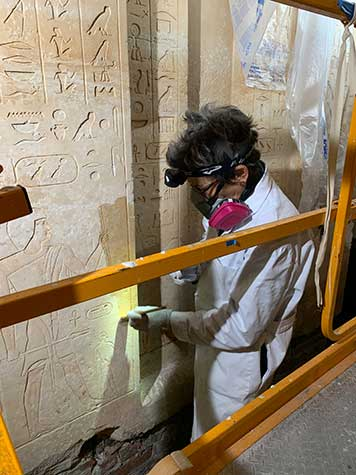 A conservator caring for the false door of Khufuankh wearing goggles and a mask