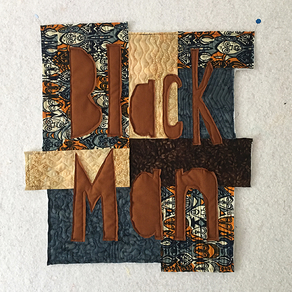 """Textile with the words """"Black Man"""" stitched over it."""