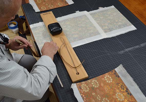 conservator rejoining reusable sections of silk