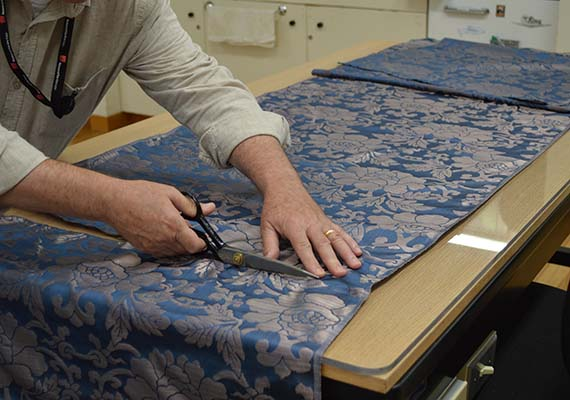 conservator cutting reproduction silk with scissors
