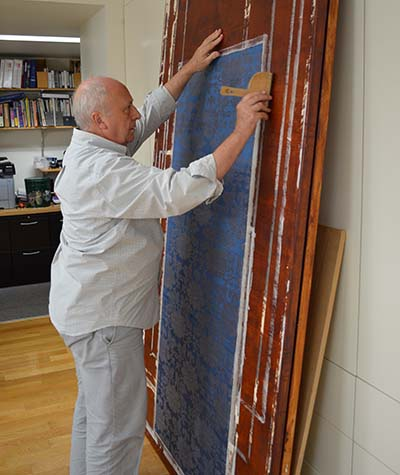 conservator stretching silk on drying board
