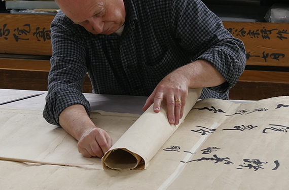 conservator detaches lining paper from scroll