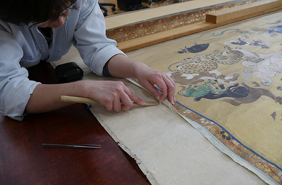 conservator detaches silk mount from painting