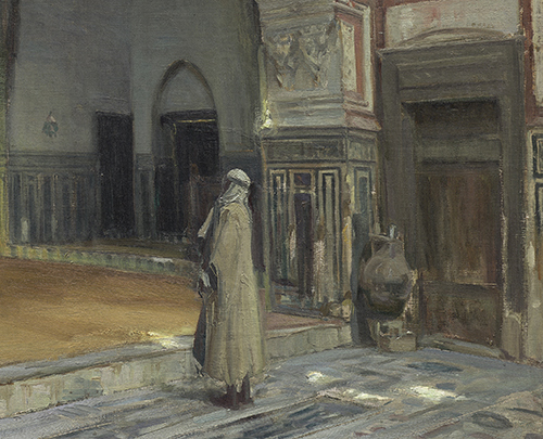 A man stands inside of a shadowy mosque and looks off at some point not shown.