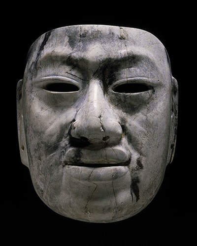 A mask depicting a solemn face carved out of gray and black jadeite