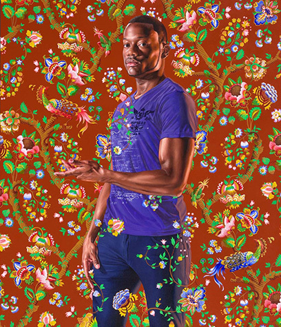 Portrait of a man in a purple shirt standing before an ornate floral background.