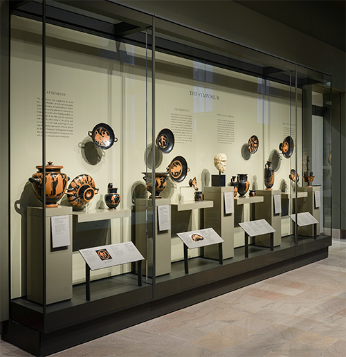 Glass display case full of ancient Greek vessels, plates, and sculpture.