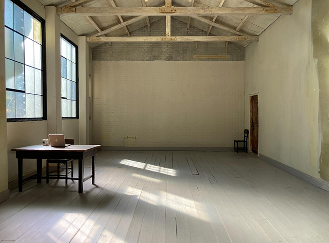 Interior of a white-walled gallery, empty except for a table with a laptop sitting on it.