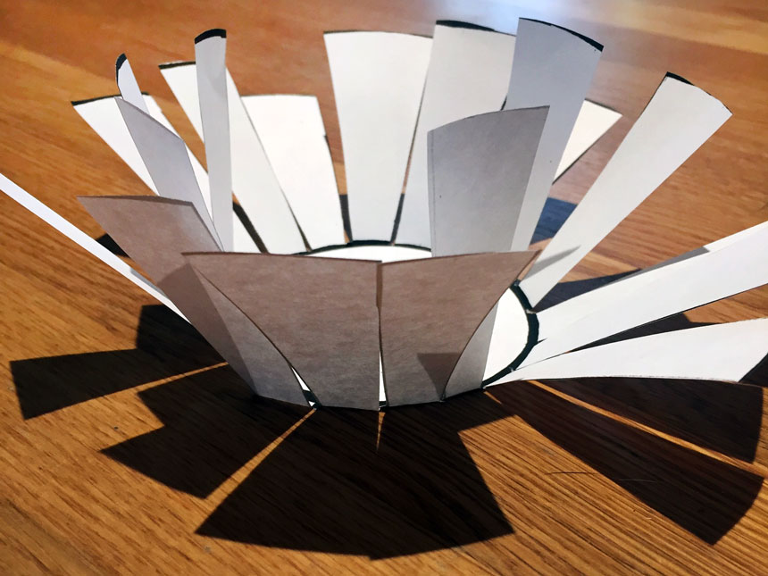 folding up strips of paper from center circle of template