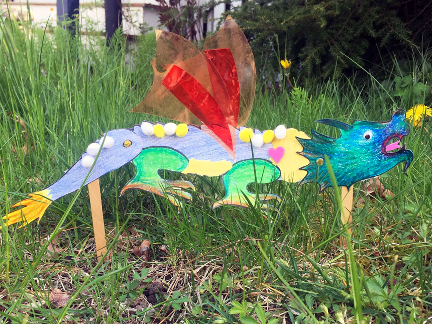 completed colorful dragon puppet planted on popsicle sticks in grass