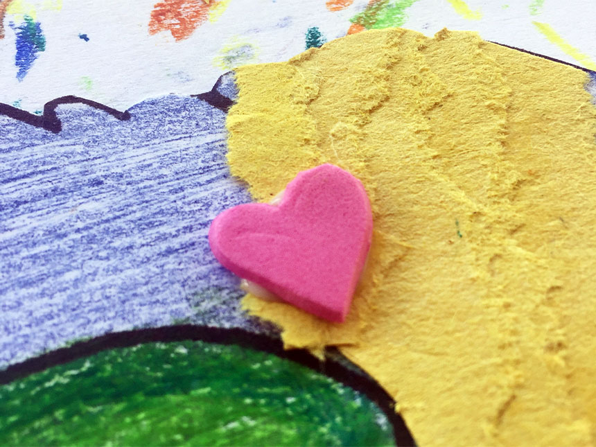 pieces of colored paper and foam heart glued onto dragon body parts