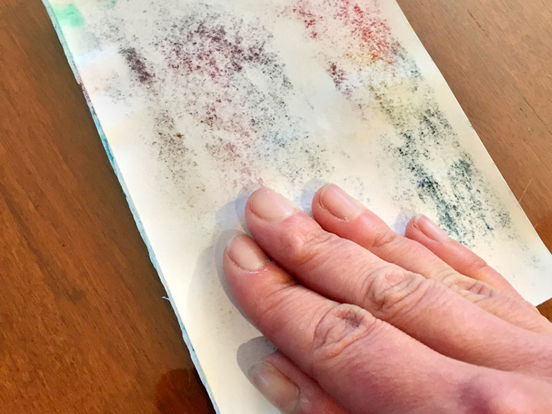 pressing surface of paper onto colored-in styrofoam
