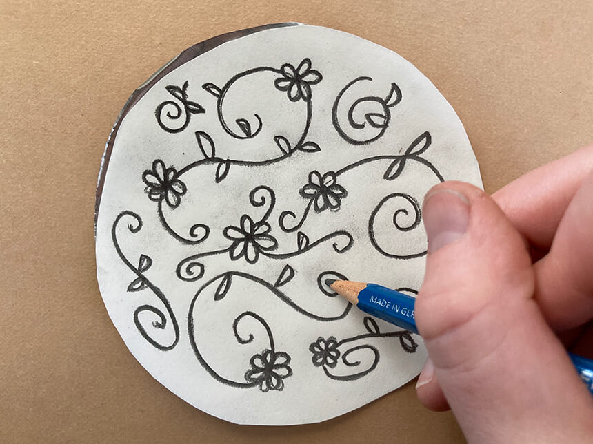 Using a pencil to trace the floral design on the paper placed on top of tooling foil