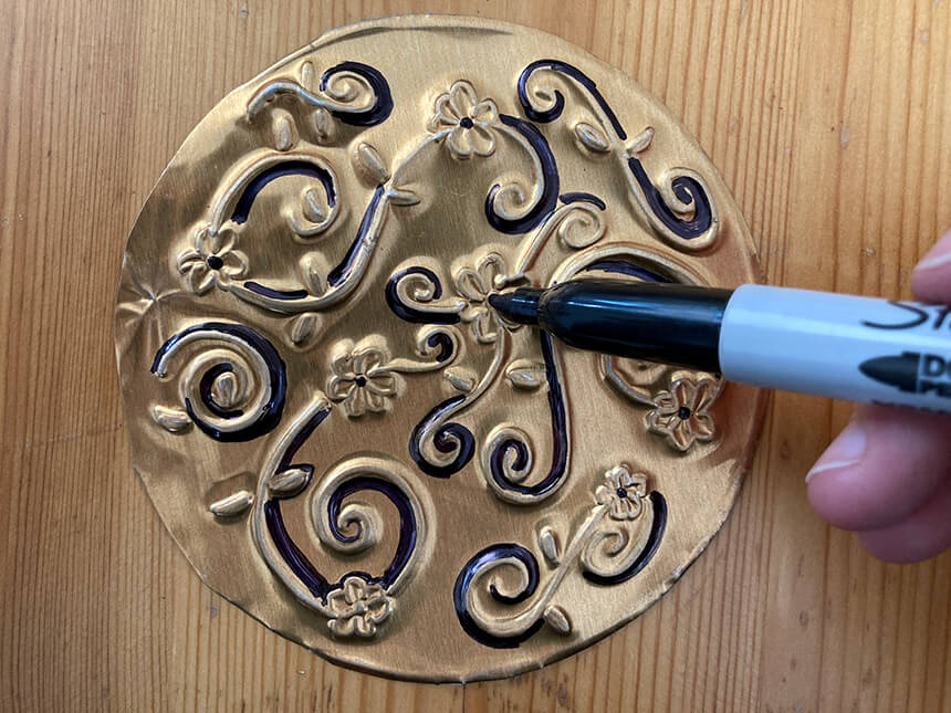 Using a marker to add color to the embossed design on the filp-side of the tooling foil