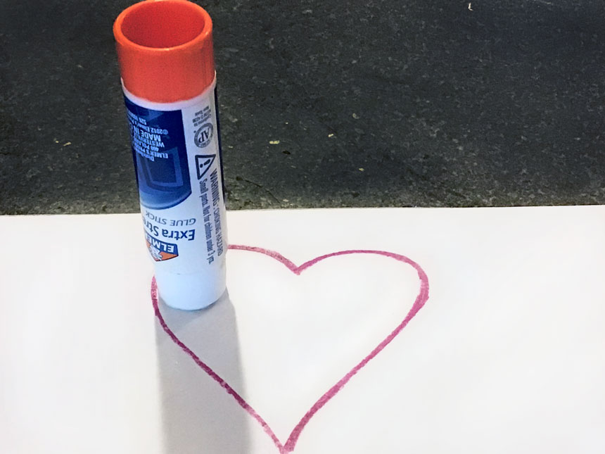 applying glue to top left of drawn heart with glue stick