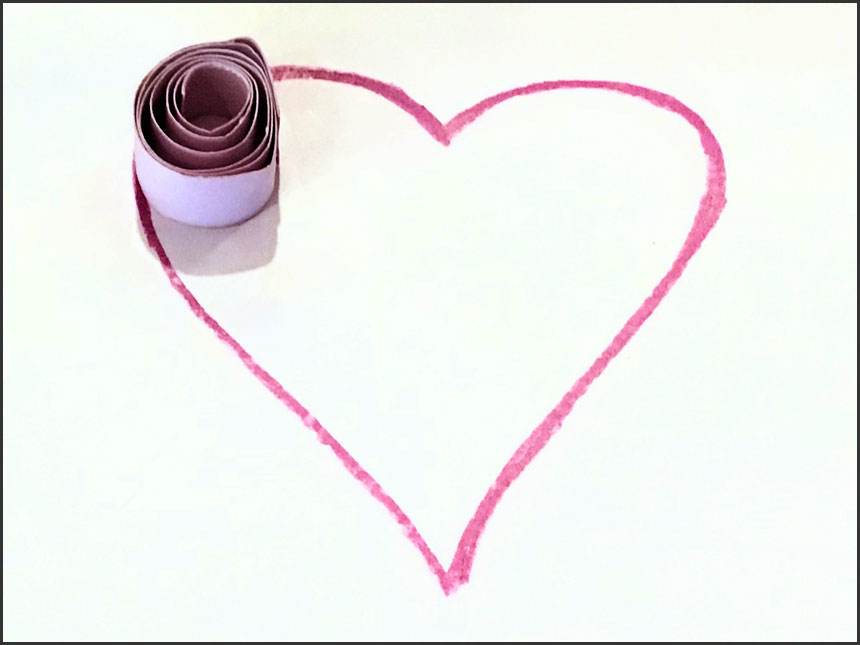 curled up strip of paper placed on top of glue on drawn heart