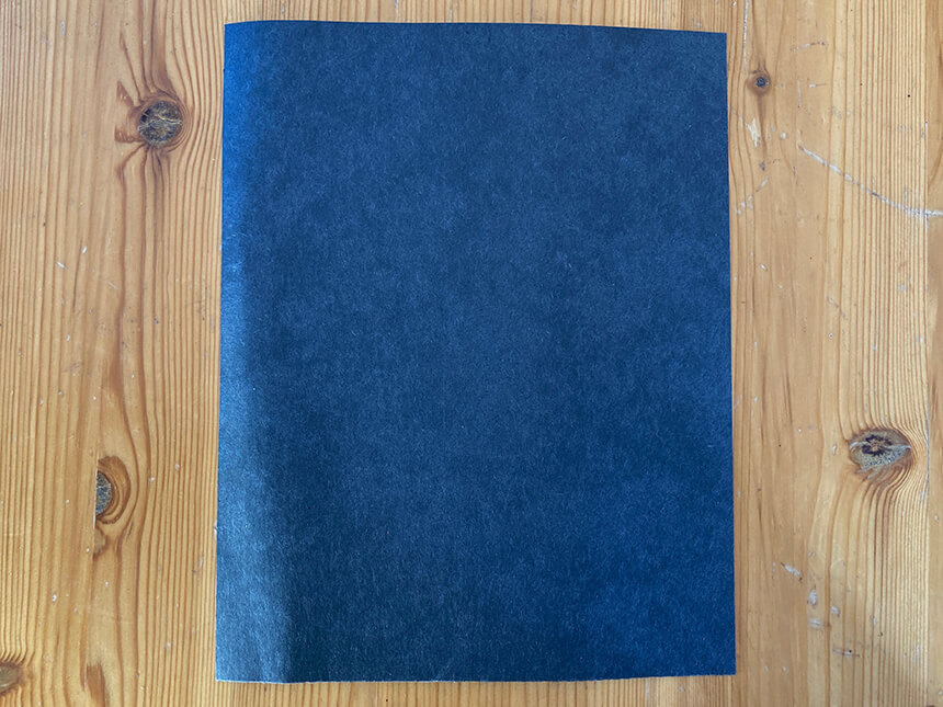 rectangle cut-out of dark blue construction paper, laid on tabletop