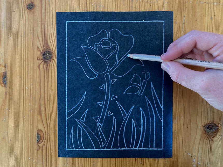 Using white colored pencil to draw outline of flower on construction paper