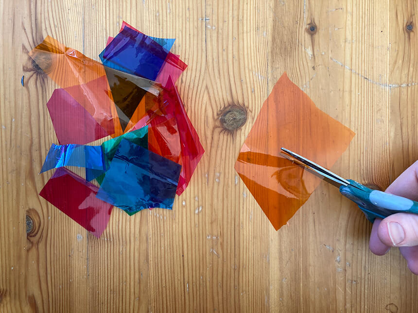 Using scissors to cut different colored cellophane into small pieces