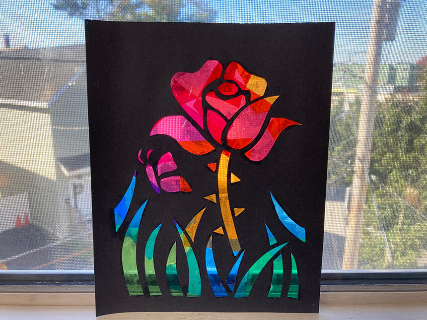 Finished stained glass art activity propped against window, with light passing through cellophane pieces arranged in shape of flower