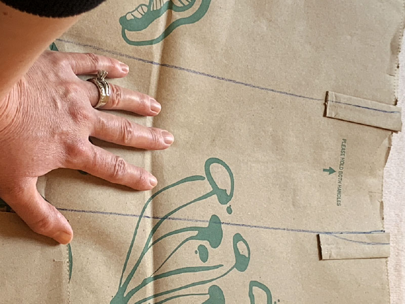 hand holding down paper bag while two vertical lines are drawn on bag
