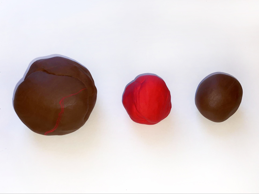 three balls of clay of different colors and sizes