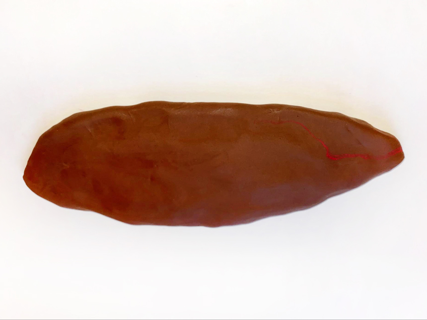 long clay oval made with large ball of brown clay
