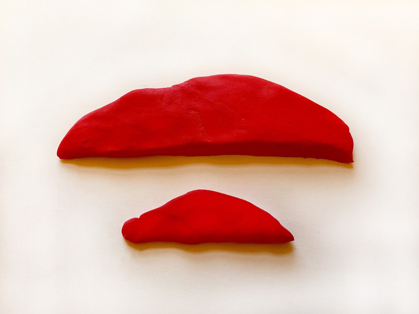 two differently sized half-oval shapes made of the same colored clay
