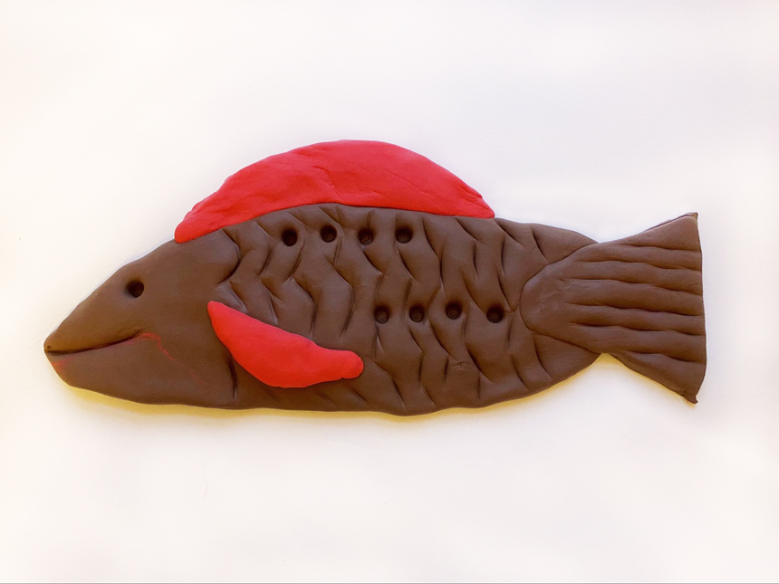 smiling clay fish with tail, scales and fins