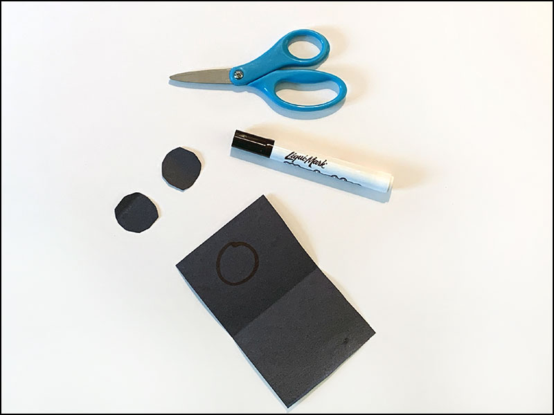 scissors and marker next to black construction paper with two circles cut out
