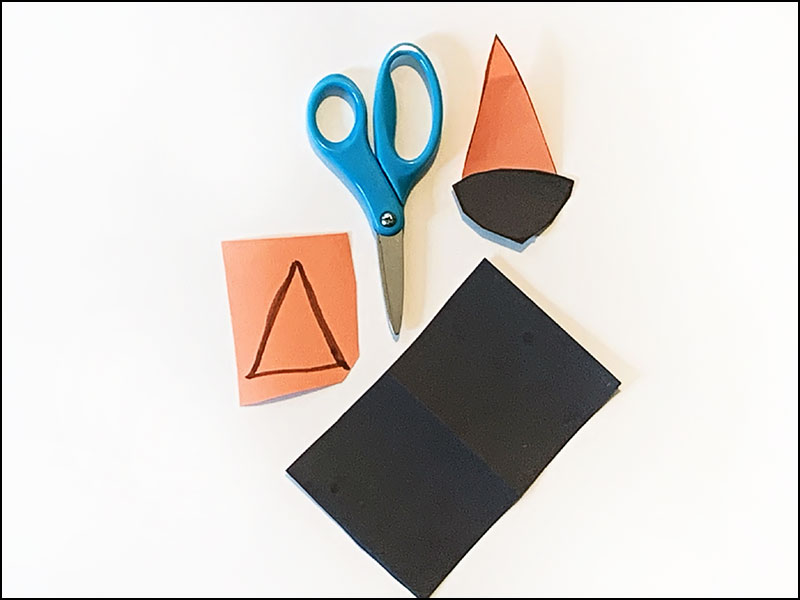 scissors next to pieces of construction paper cut to various shapes