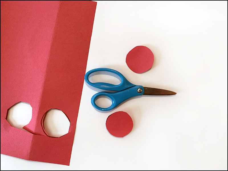 scissors next to red construction paper with two red circles cut