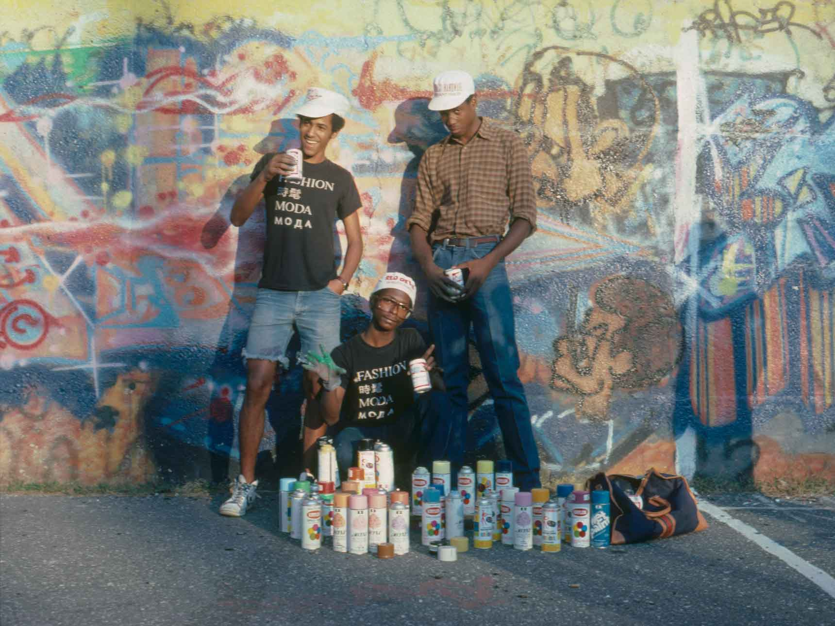 three artists with spray paint posing in front of graffiti-covered wall