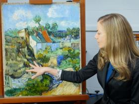 curator pointing to van Gogh painting on easel