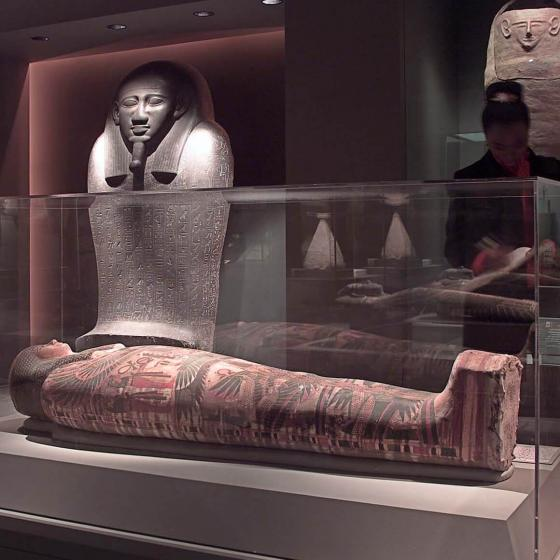 View of Egyptian Funerary Arts Gallery, with visitors looking at mummy inside case