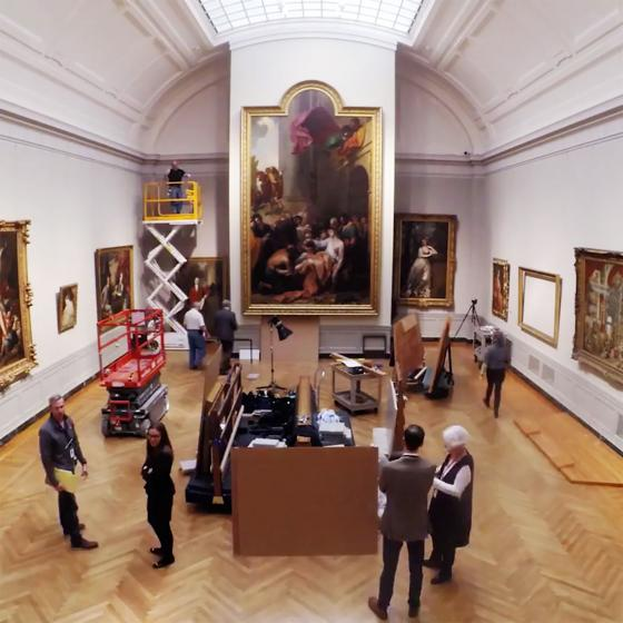 Museum staff installing paintings in European gallery