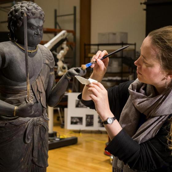 Conservator uses brush to gently remove dust from Buddhist sculpture