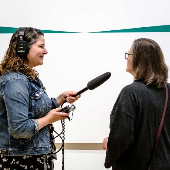 podcast host holding microphone towards Museum visitor in front or Herrera painting