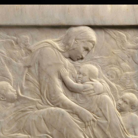 marble relief depicting the Madonna surrounded by angels and wispy clouds holding child